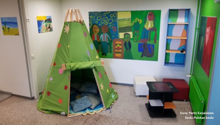 Kuva tilasta, jossa on paljon erilaisia taide-esineitä, kuten maalauksia sekä vihreä teltta, jonka sisään on mahdollista ryömiä.
