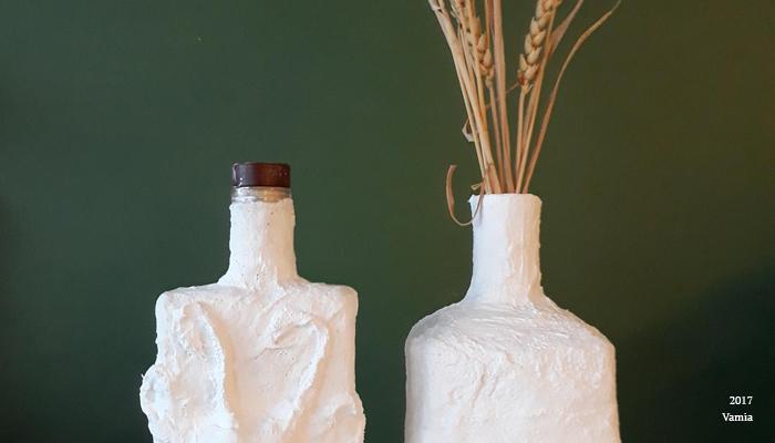 Yksityiskota valokuvasta. Kaksi valkoista, kipsista pulloa asetettuna vierekkäin tummanvihreää taustaa vasten. Toisessa pullossa on ruskea korkki ja toiseen on laitettu oljenkorsia.