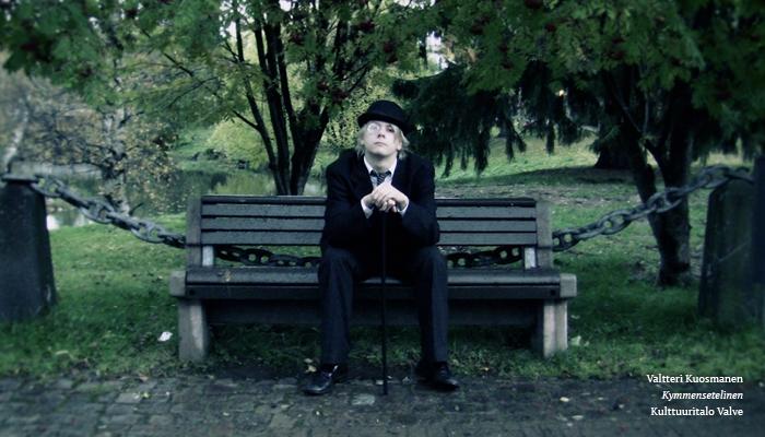 Still-kuva elokuvasta. Kuvassa on puistonäkymä. Kuvan keskellä puiston penkillä istuu mustaan pukuun, mustiin kenkiin, monokkeliin ja knallihattuun pukeutunut henkilö, jolla on kädessään musta kävelykeppi. Henkilön ilme on vakava ja sää pilvinen.